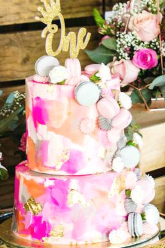 Gorgeous pink, white and coral tiered birthday cake decorated with pink and grey macarons and meringues, topped with a gold 'one'