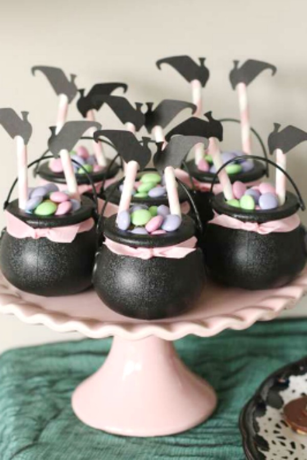 Mini cauldrons full of candy with an upside down witch sticking out