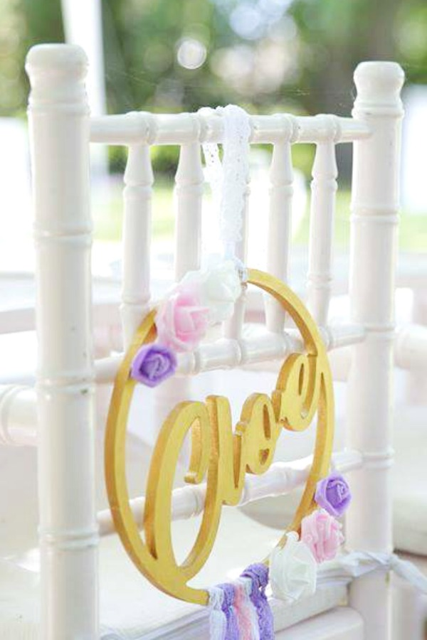 Beautiful personalized name decorations hanging on each chair at this wonderful boho chic baptism