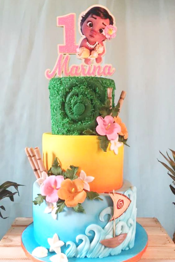 A beautiful tiered birthday cake topped with an adorable baby Moana