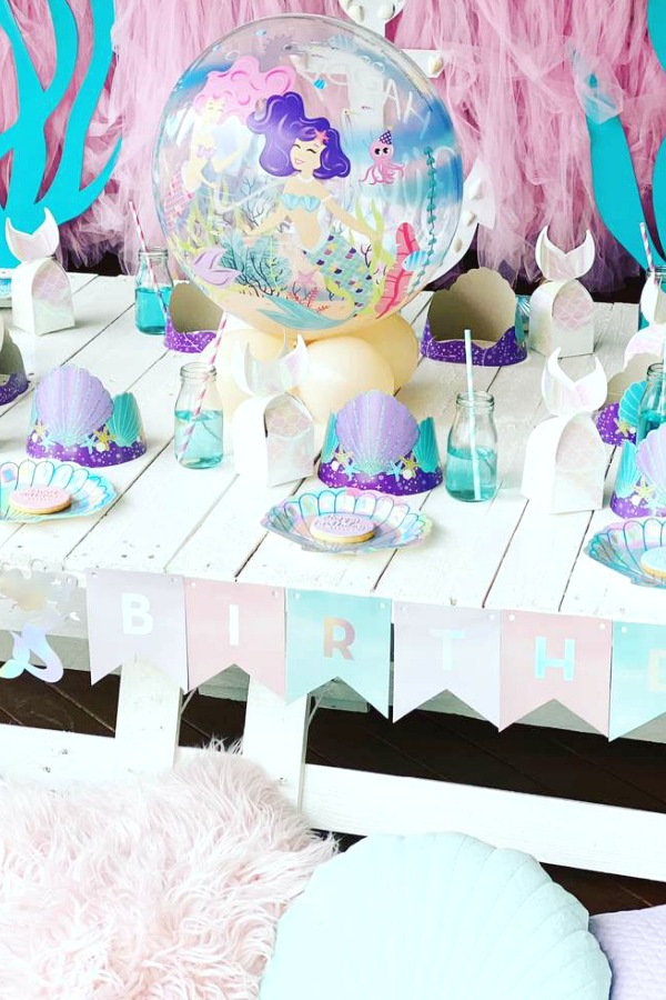 Stunning table settings with shell plates, mermaid paper crowns, mermaid tail party favor boxes, and a dazzling foil mermaid balloon centerpiece